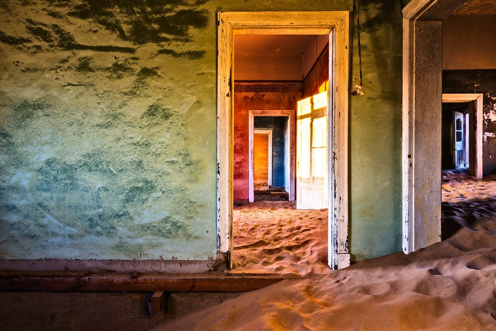 Kolmanskop - An abandoned jewel rises in the middle of the desert, just few steps away from the Atlantic Ocean. It is a pearl of beauty and silence as the majestic desert that embraces it. This small ghost town built in the middle of nothing and enclosed only by sand dunes, it is what remains of the un- bridled diamond rush, a remote past that no longer exists.Under the first morning lights, a thin and crisp fog rises from the ocean, creating a ghostly atmosphere. The sand dunes, that have invaded the houses, shine of golden hues, and the bright colours of the crumbling ruins' walls, con- quered by the desert, catch everyone's eyes.