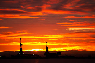 Fiery sky behind two drilling rigs, one rotary the other coil.