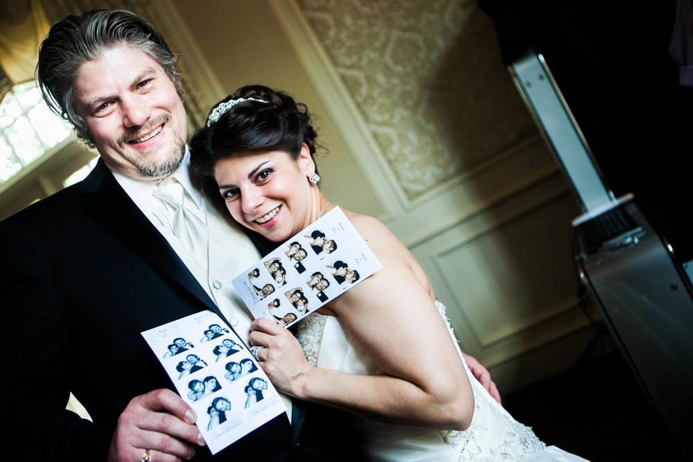 bride and groom with photobooth strips photograph by westchester wedding photographer