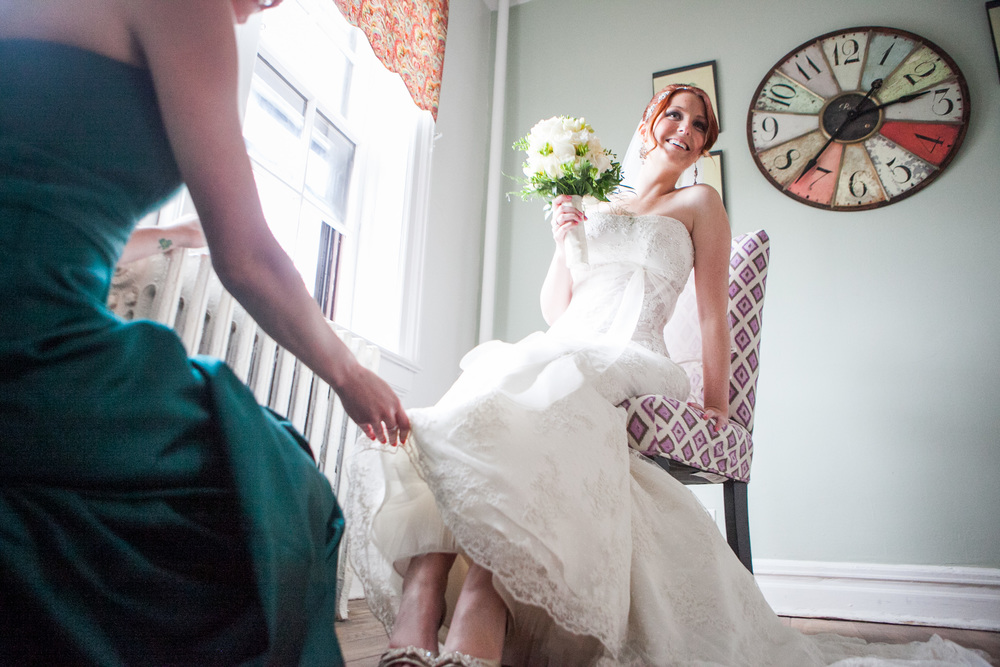 bride putting shoes on by westchester wedding photographer