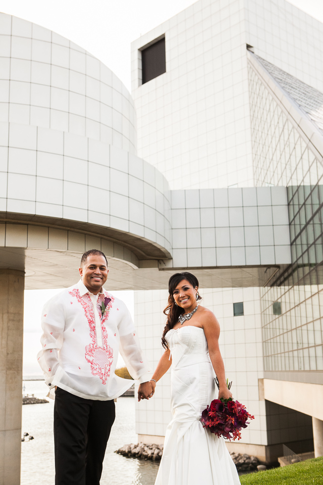 bride in groom in front of rock and roll hall of fame
