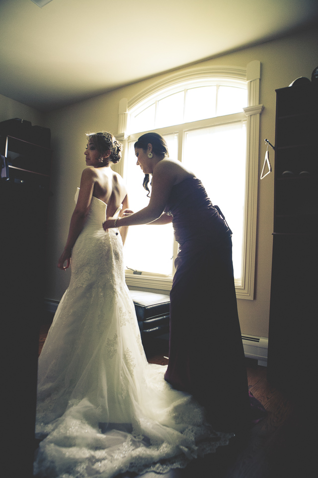 Sister zipping up bride's dress.