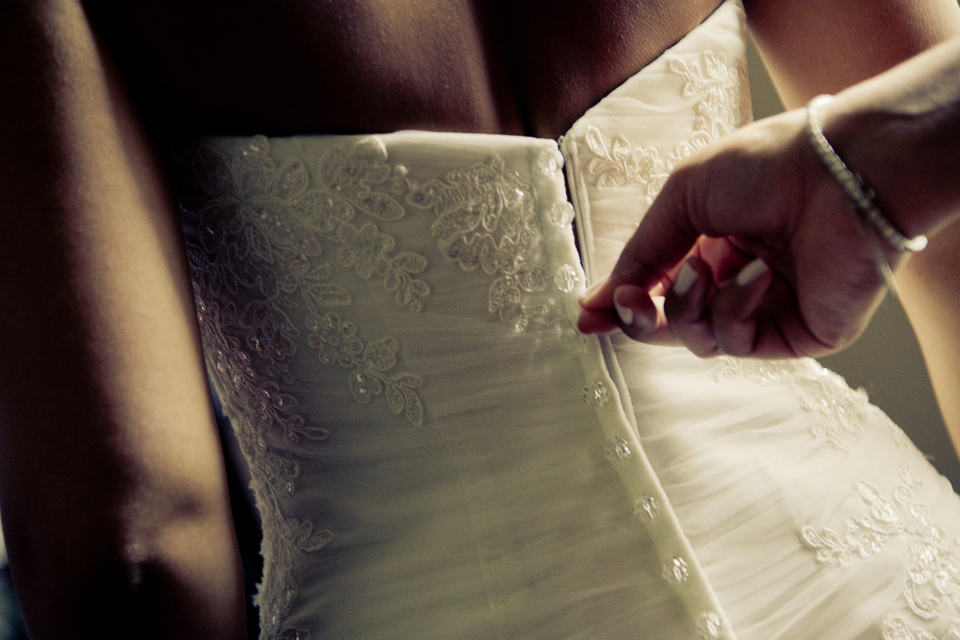 Back of bride's wedding dress being zipped.