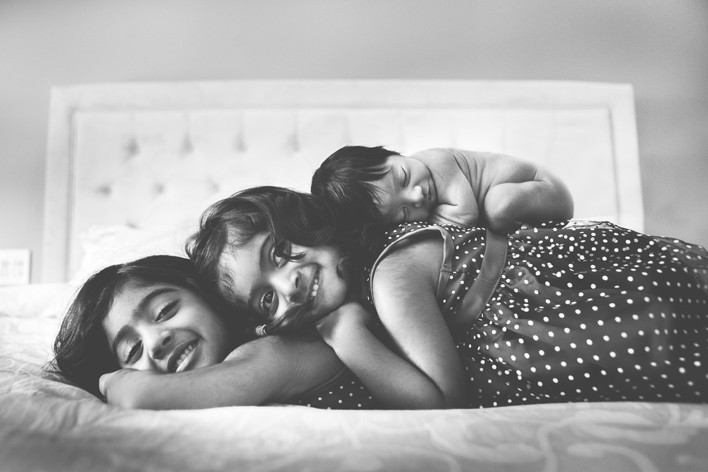 Newborn laying on top of sisters by Westchester wedding photographer Sage Studios Photography.
