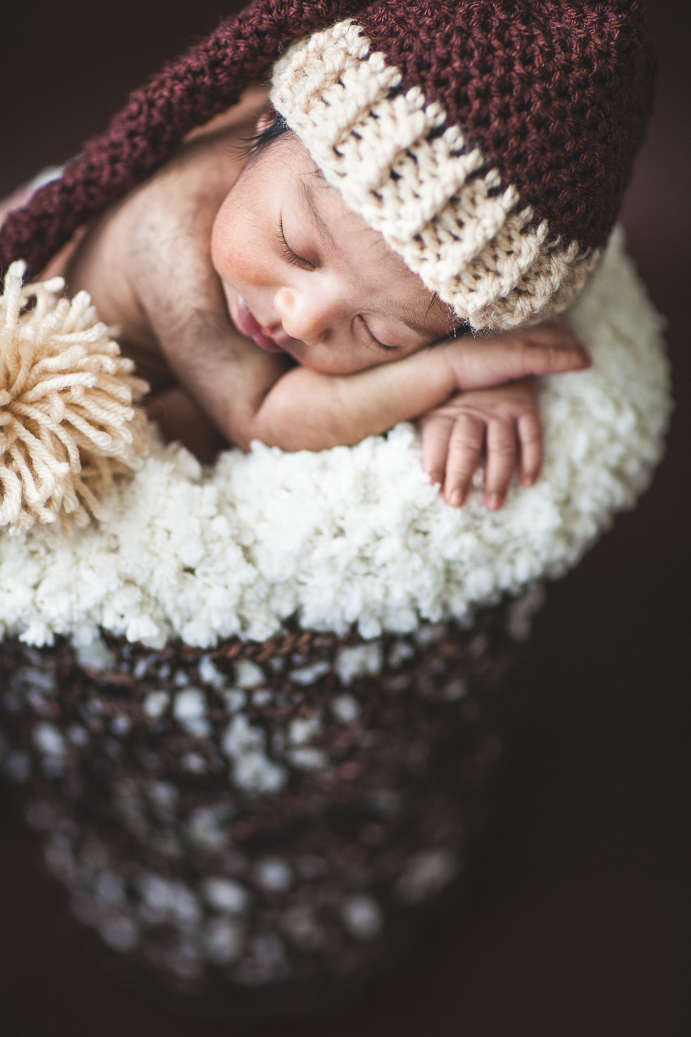 Newborn photo in brown basket and brown cap by Westchester wedding photographer Sage Studios Photography.
