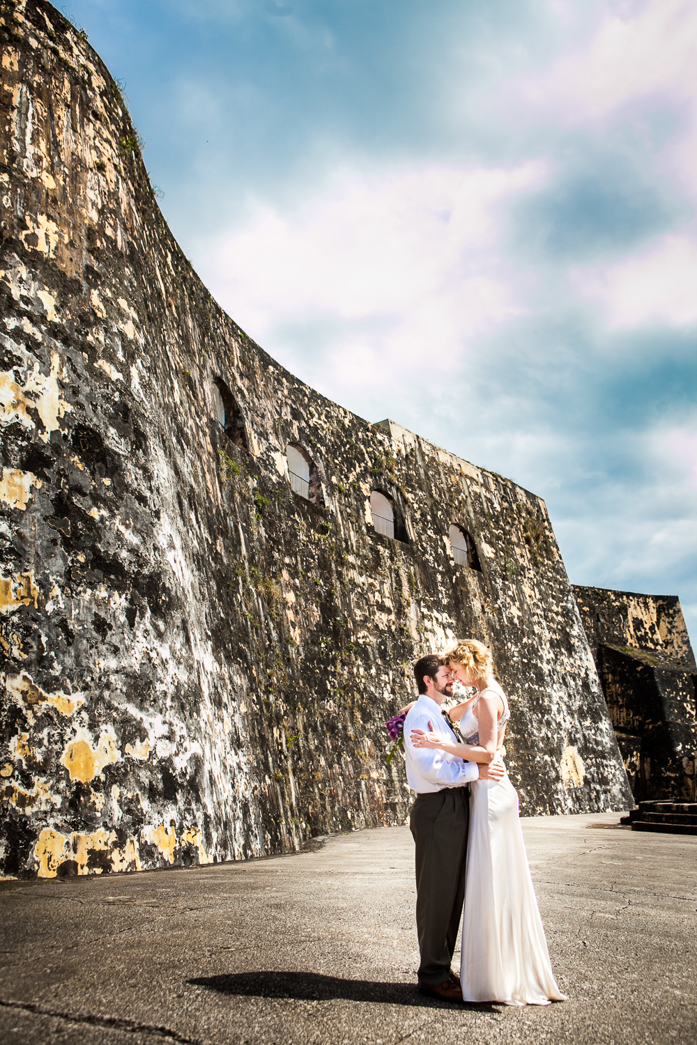 Bride and groom slow dance at Castillo San Felipe del Morro in Puerto Rico, by Westchester photographer Sage Studios Photography.