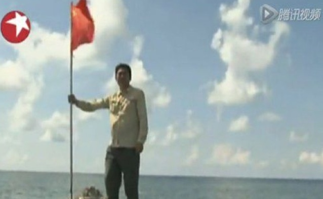 A viral photo of an unidentified Chinese journalist planting a flag on the reef of Scarborough Shoal