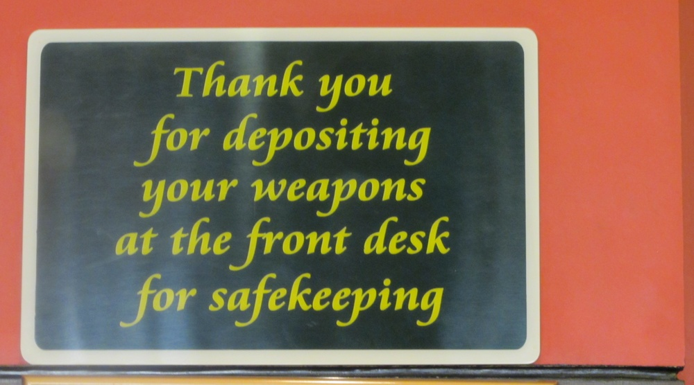 "The surprising hotel counter sign: ""Thank you for depositing your weapons at the front desk for safekeeping.""  (Photo by Lisa Suguitan Melnick)"