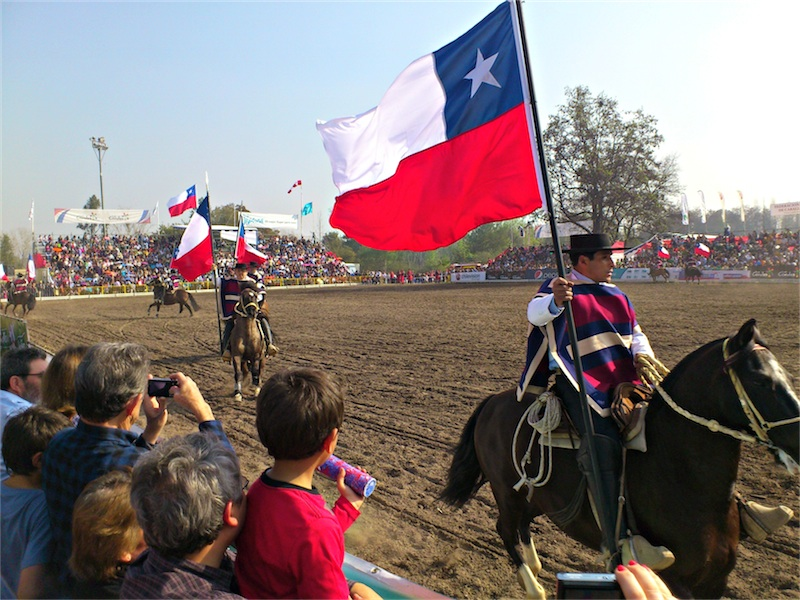 Chilean  huasos  wave the national flag in a rodeo show during Dieciocho, the country's Independence Day celebrations.  (Photo by Migs Bassig)