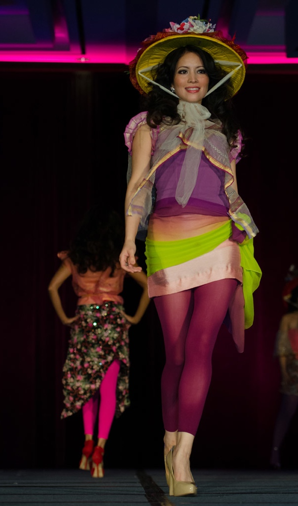 Multilayered ensemble consisting of sheer vest, lavender and purple top, pink miniskirt with lime and peach sash, violet leggings. A multicolored floral hat completes the ensemble. A Patis Tesoro creation at the annual fashion show fundraiser of the Philippine International Aid (PIA) in San Francisco, November 2012.
