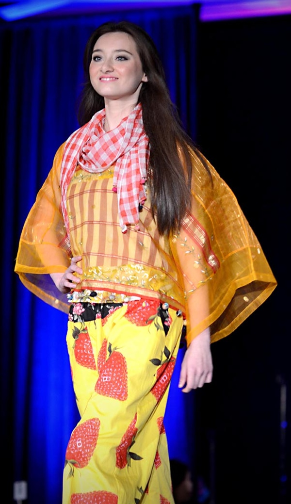 Gold sheer waist-length kaftan over yellow harem pants with large strawberry prints. A red and white plaid scarf completes the ensemble. A Patis Tesoro creation at the annual fashion show fund raiser of  the Philippine International Aid (PIA) in San Francisco, November 2012.