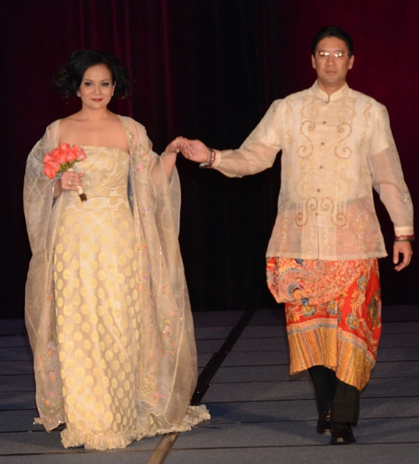 Ecru damask strapless wedding gown with a floor-length piña kaftan embellished with multicolored pastel embroidery. The male model wears an ecru embroidered barong over an orange and gold malong and black pants. A Patis Tesoro creation at the annual fashion show fundraiser of the Philippine International Aid (PIA) in San Francisco, November 2012.
