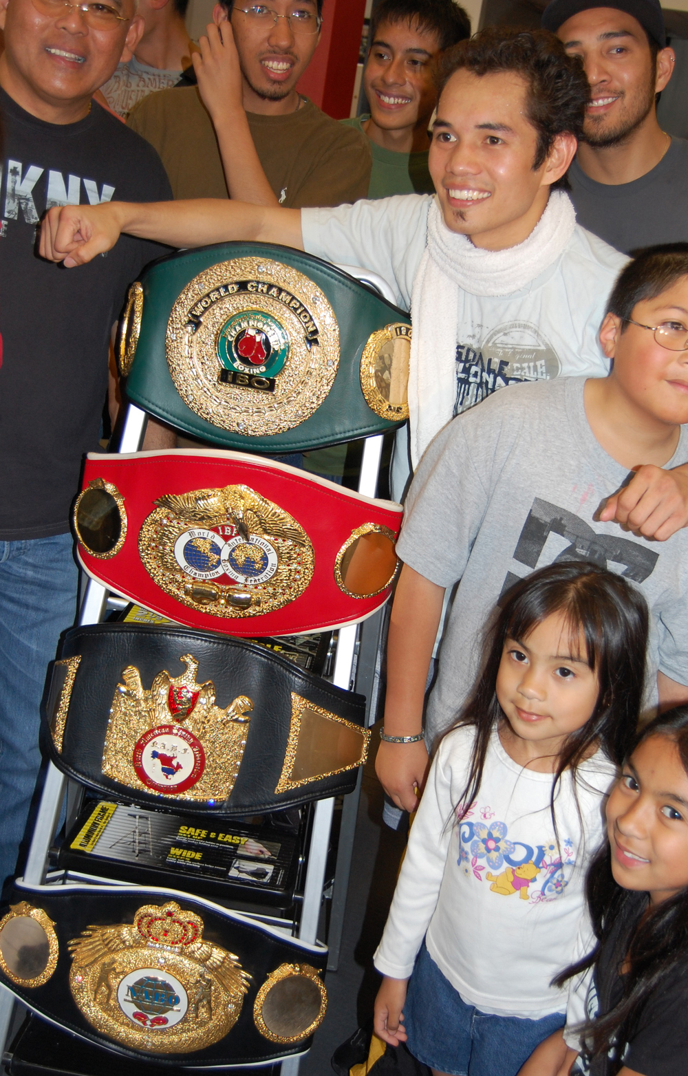 Nonito Donaire, Jr., shown here with fans, displays his championship belts. He retained his WBO super bantamweight title by knocking out Jorge Arce in the third round of their December 15, 2012 bout.   (Photo by Raymond Virata)