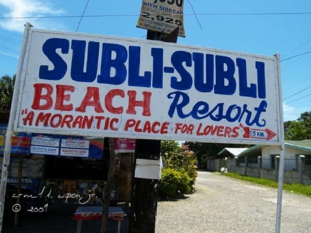 "Sign displays: ""Subli-Subli Beach Resort 'A Morantic Place for Lovers' 15 KM."""