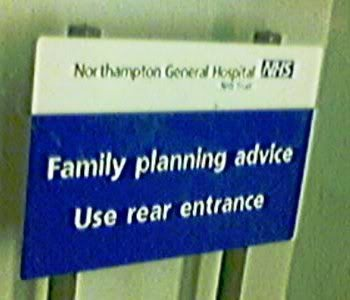 "Sign displays: ""Northampton General Hospital. Family planning advice. Use rear entrance."""