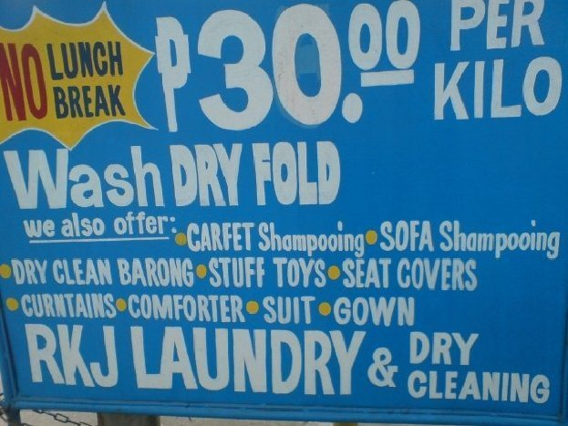 Sign says: No lunch break. P30.00 per kilo. Wash. Dry. Fold. We also offer: Carfet Shampooing. Sofa Shampooing. Dry clean barong. Stuff toys. Seat covers. Curntains. Comforter. Suit. Gown. RKJ Laundry & Dry Cleaning""