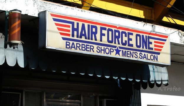 "Sign displays: ""Hair Force One Barber Shop Men's Salon"""