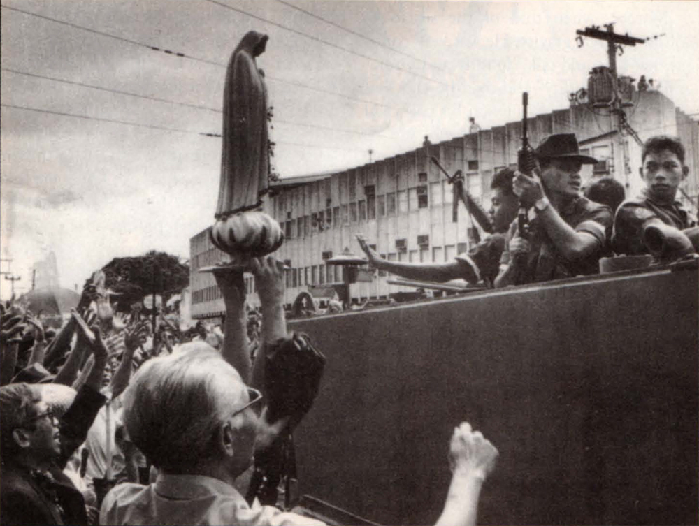 Unarmed civilians with religious symbols surrounded tanks and soldiers in EDSA and ensured a relatively peaceful resolution to the crisis.  (Photo by Linglong Ortiz)