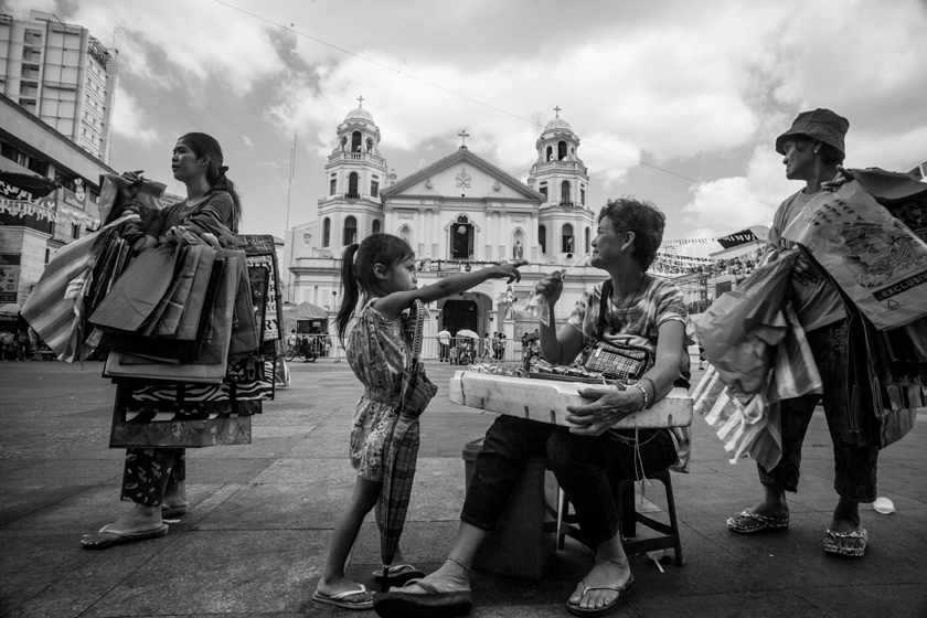 Mother and daughter selling bags in front of Quiapo Church. Andrea is a 32-year-old mother of six; the oldest is nine years old and growing up in Quiapo.  (Photo by Rick Rocamora)