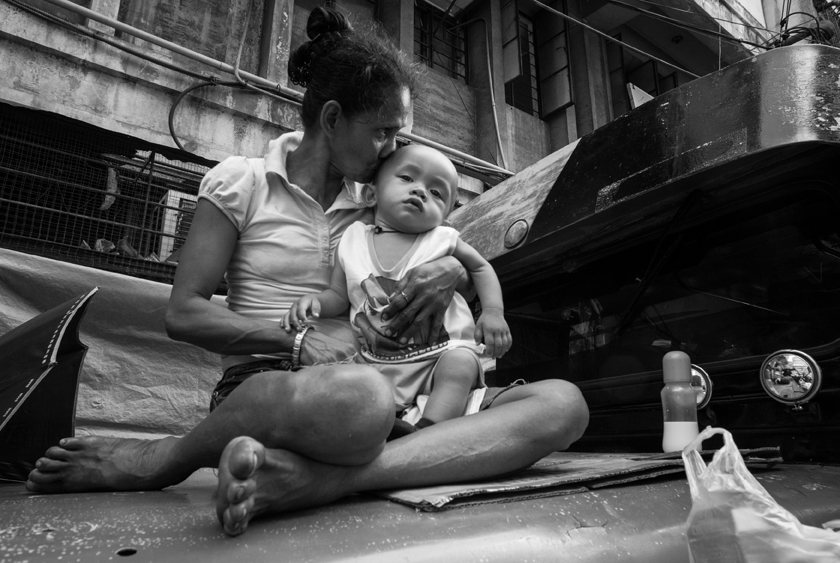 Emy and Cholo, who was abandoned by his mother and left to Emy, who is also homeless, and born and raised in Quiapo.  (Photo by Rick Rocamora)