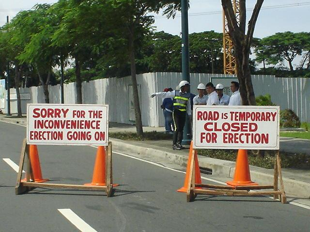 Road signs somewhere in Metro Manila: Sorry for the Inconvenience, erection going on and Road Is Temporary Closed for Erection