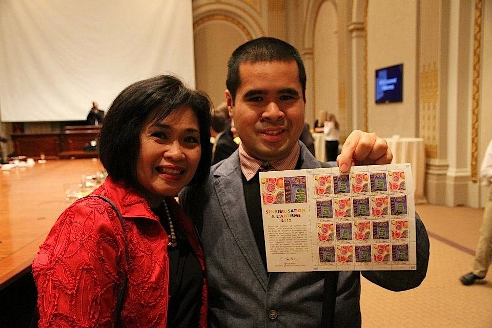 J.A. and his mom, Marie Zelie, at the New York Stock Exchange in 2012, showing the U.N. stamp that featured his painting (Photo by Vincent Tan)