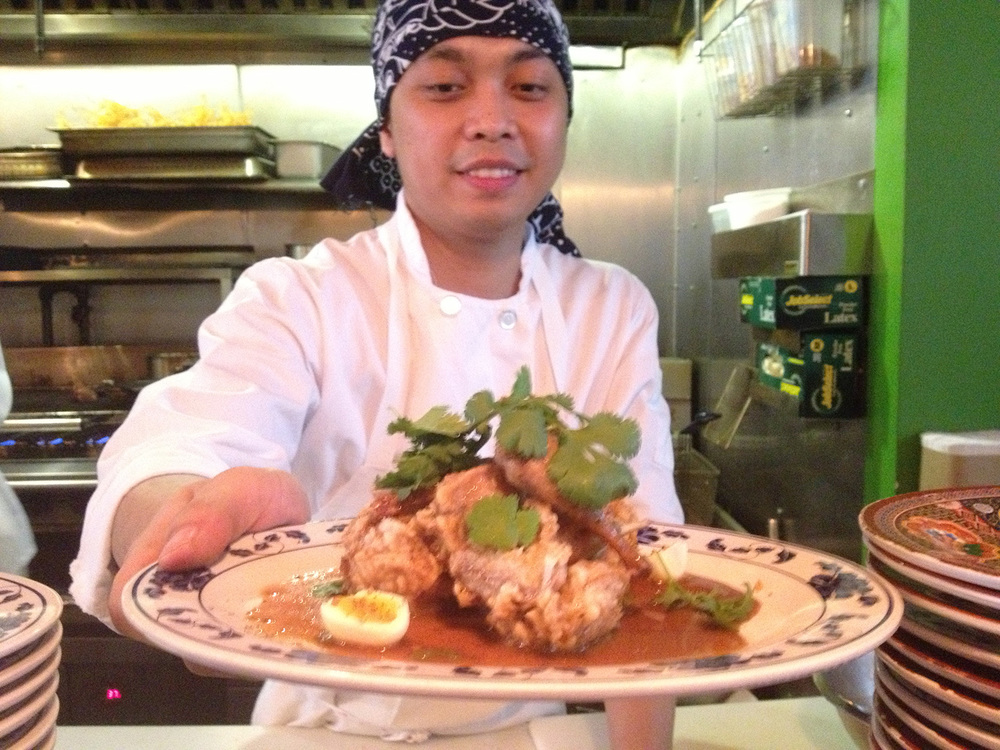 Pig and Khao's Filipino line cook Jesse serves up the Quail Adobo, which is deep fried with soy sauce, vinegar, Szechuan peppercorns and crispy garlic.  (Photo by Elizabeth Ann Quirino)