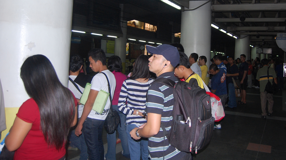Commuters await the train at the MRT station in Quezon City, Philippines. (Photo by Raymond Virata)