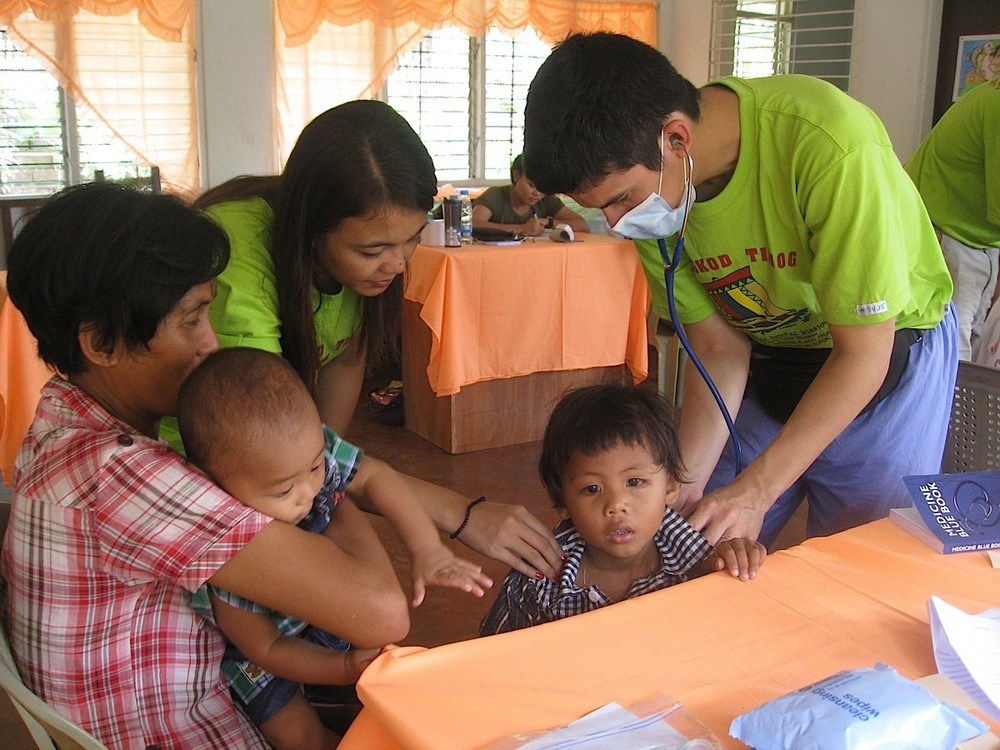 "Attending to patients at the medical mission site in Taytay, Palawan, and working ""shoulder to shoulder"" (balikatan) with a civilian Filipino nurse, who also acted as a Tagalog interpreter (Photo courtesy of Tiago Villanueva)"