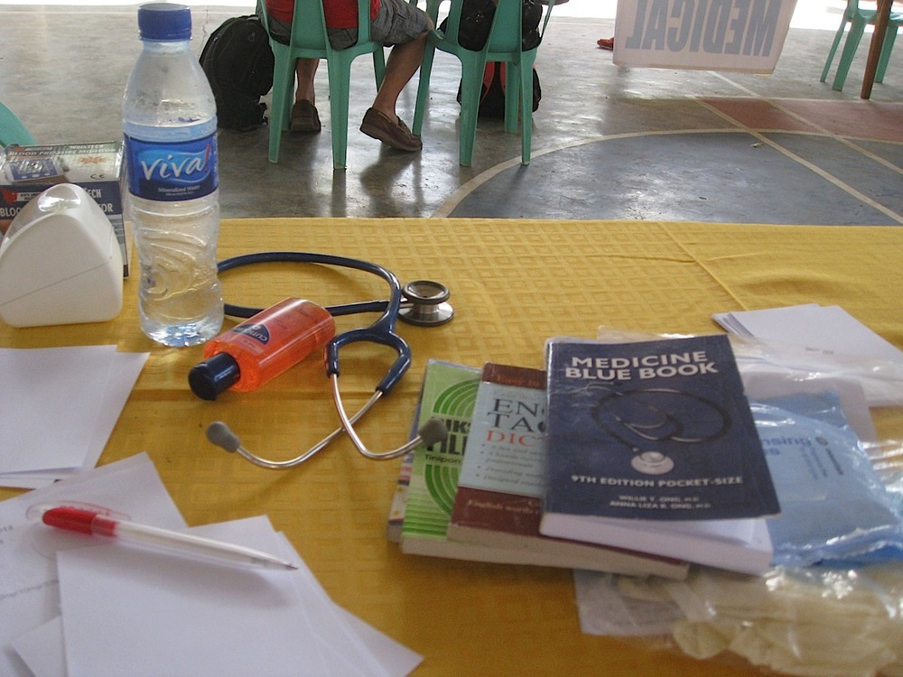 "Some must-haves on the ""office desk"" during a medical mission in The Philippines: water, anti-bacterial hand gel, tissue wipes, gloves, surgical masks, the Philippine's ""Medicine Blue Book"", and an English-Tagalog and a Tagalog-English dictionary. (Photo courtesy of Tiago Villanueva)"