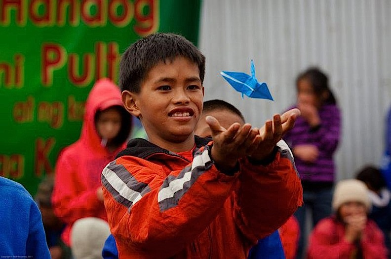 A young boy In Bashoy, Benguet enjoying the origami he made with Japanese volunteers. (Photo by Rick Rocamora)