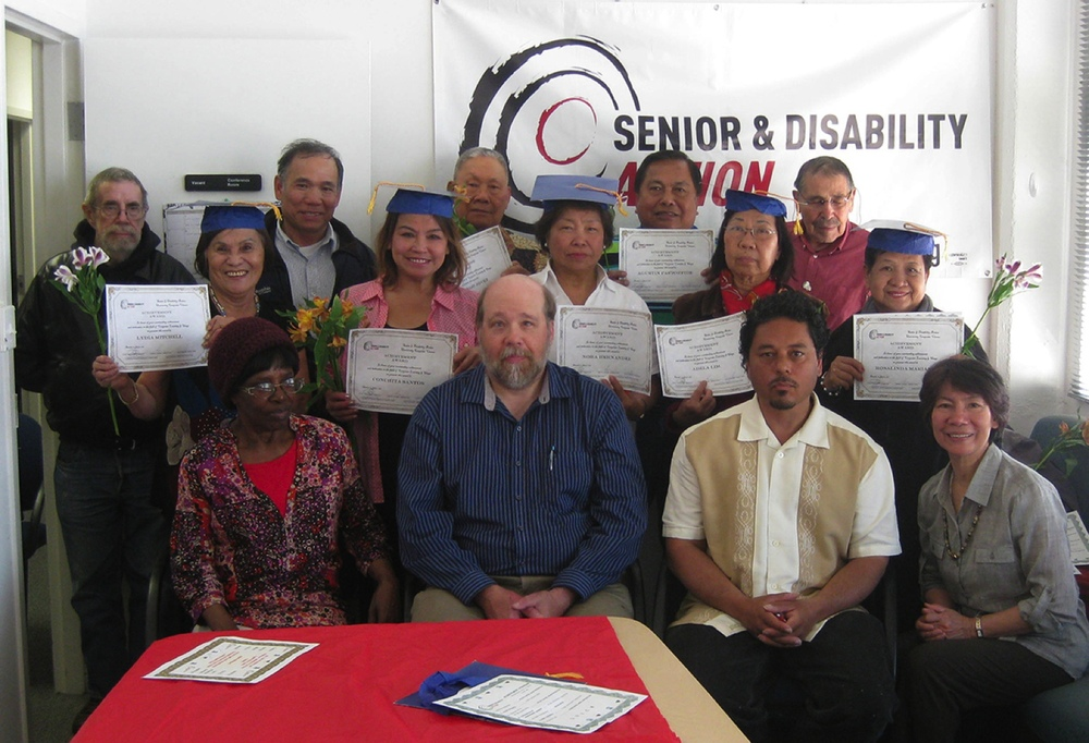Graduation day of the Filipino seniors taking the computer class. Seated are the staff: Constance Smith, class volunteer; Pi Ra, computer class program head; Tony Robles, housing organizer; and Helen Carter, computer class instructor (Photo courtesy of Senior and Disability Action)