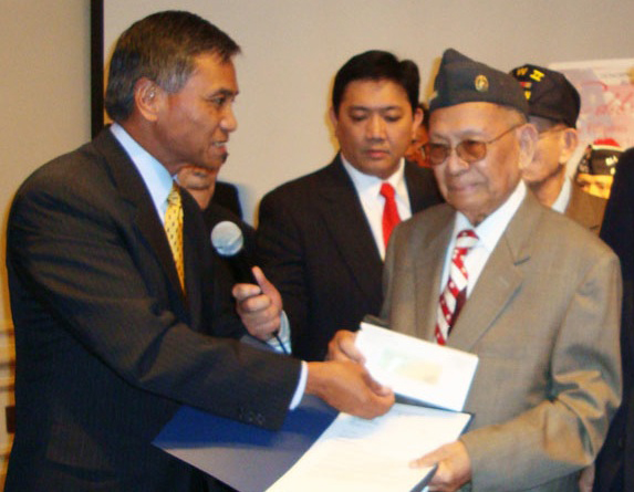 Maj. Gen. Antonio Taguba presents a $15,000 check to Alberto Bacani, the first of the many Filipino World War II Veterans to receive compensation after the  American Recovery and Reinvestment Act (ARRA) was signed into law on February 13, 2009. (Source: New America Media)