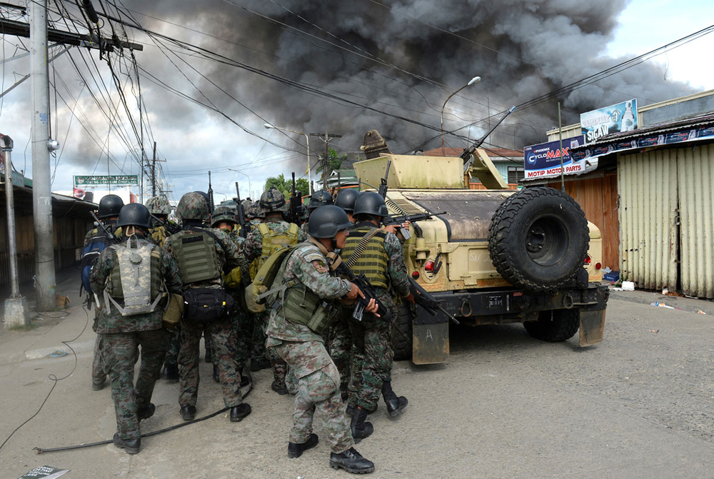 Philippine National Police special forces advance during a firefight with the MNLF in Zamboanga (Photo by Ted Aljibe/AFP)