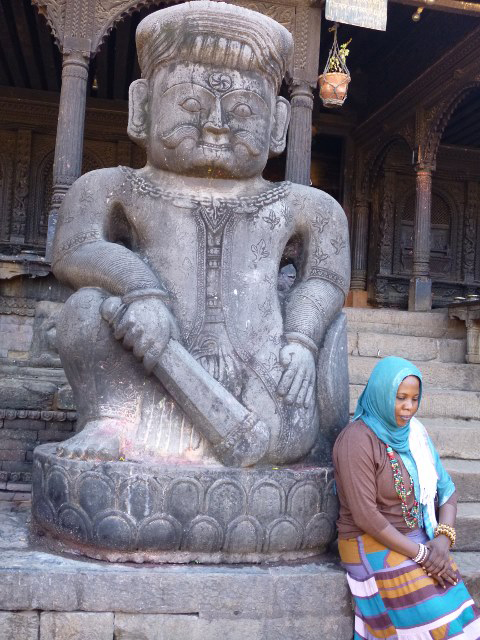 A woman rests beside a stone statue guarding a temple in Bhaktapur's Dattaraya Square (Photo by Paulynn Sicam)