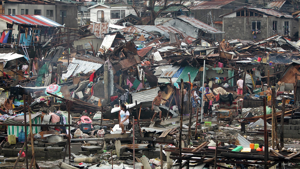 Filipino storm victims check out the damage to their community after Typhoon Yolanda (Haiyan) hit the Philippines. (Source: sbs.com.au)