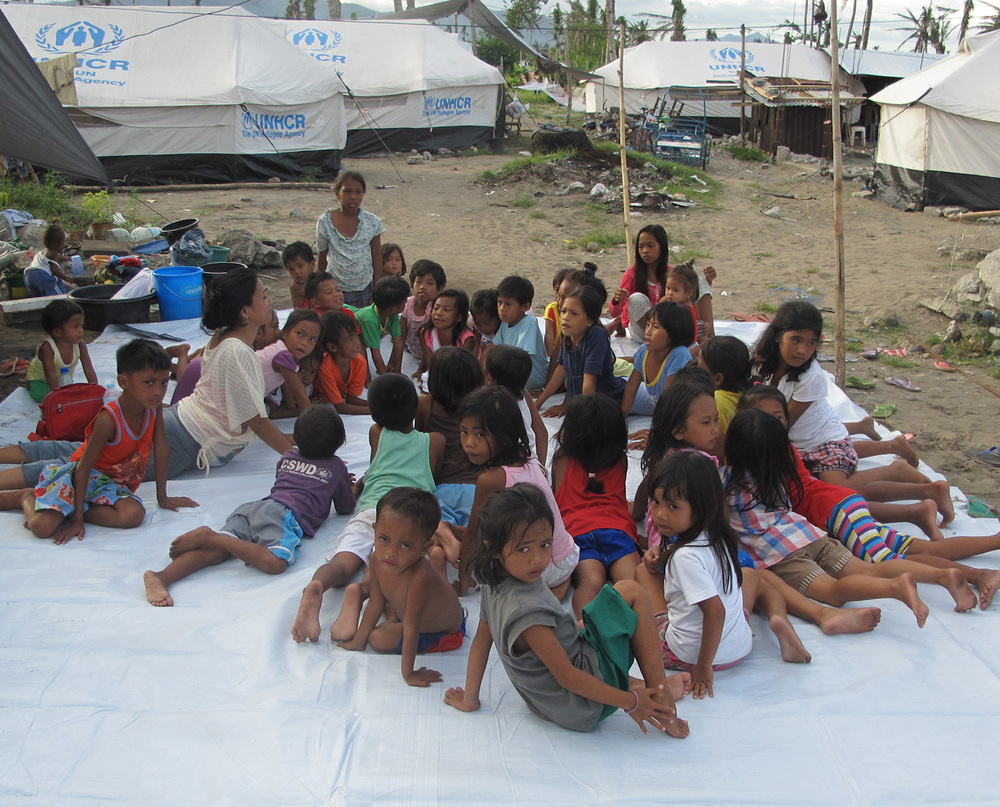 Sonya leading children in yoga in Barangay 89-90 Tacloban City. (Photo courtesy of Rene J, Navarro)