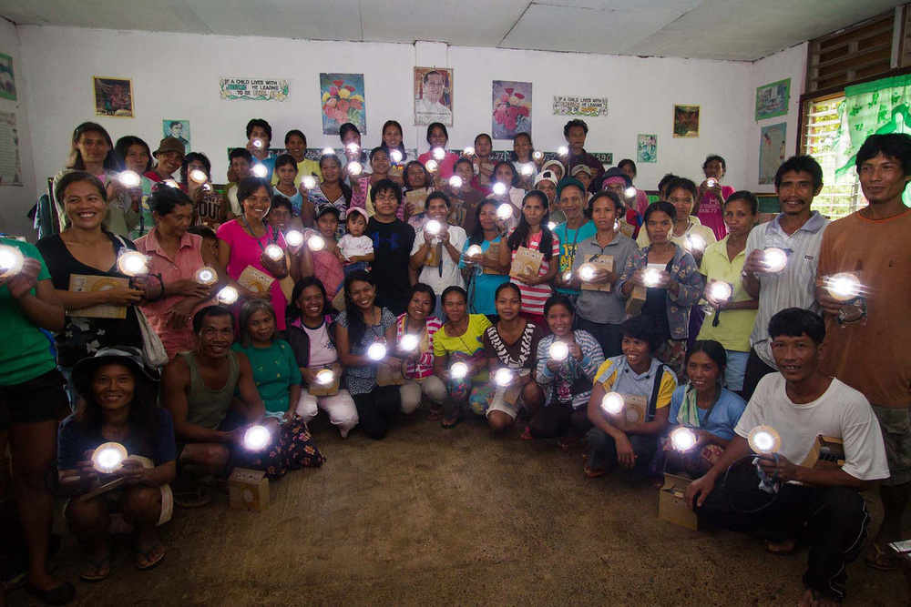 Beneficiaries flash on their solar lamps  (Photo by Chris Yuhico)