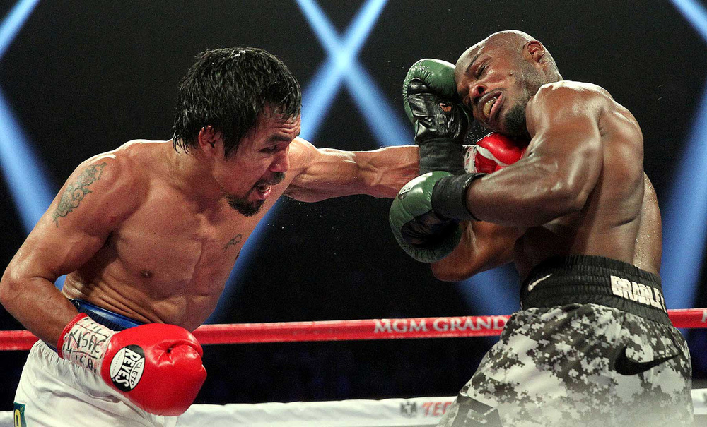 Manny Pacquiao (left) beats Timothy Bradley by unanimous decision for the WBO Welterweight title (Photo by Chris Farina/Top Rank)