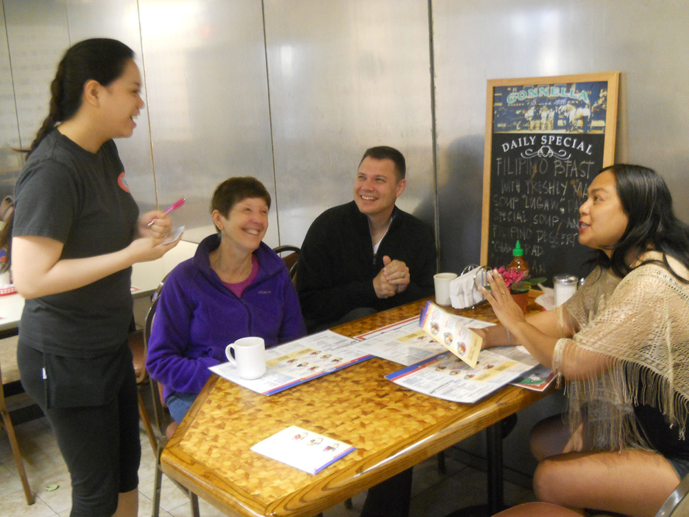 Aya Gogliotti (standing) describes the Filipino breakfast at Uncle Mike's Place to Joan Vande Kieft, Mark Magajne, and Sandra Masibay. (Photo by Ivan Kevin R. Castro)