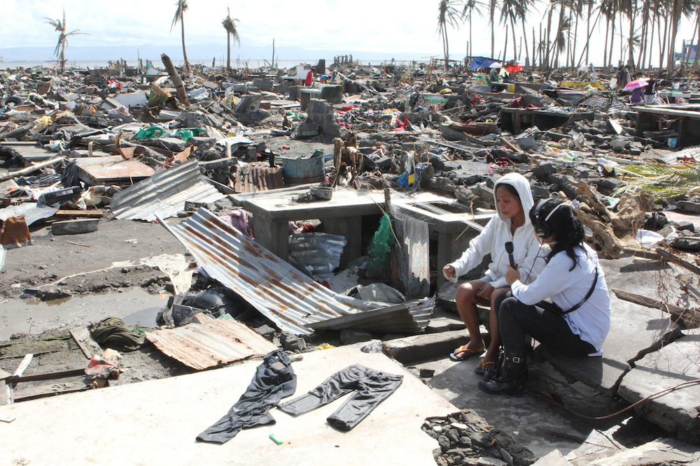 The author interviewing a survivor in Barangay 88, Tacloban, a few days after Typhoon Haiyan. (Photo by Ron Hose)