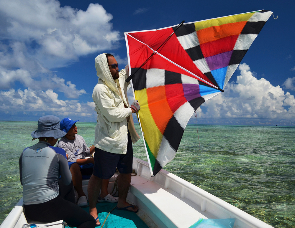 Engineer Jaylord Jauod from the Mapua Institute of Technology prepares to deploy a kite. Its images will give researchers a bird's-eye view of Tubbataha's twin scar sites. (Photo by Gregg Yan/WWF)