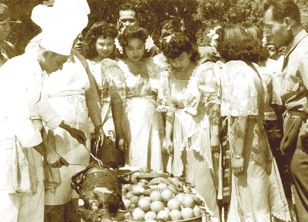 Filipino American GI trainees enjoy a Sunday lechon (roast pig) parties with civilians; Patricia Todtod (third from right) is the first Filipino woman to edit a newspaper, the Philippine Mail of Salinas, California. (Photo from the Alex Fabros Sr. Collection)