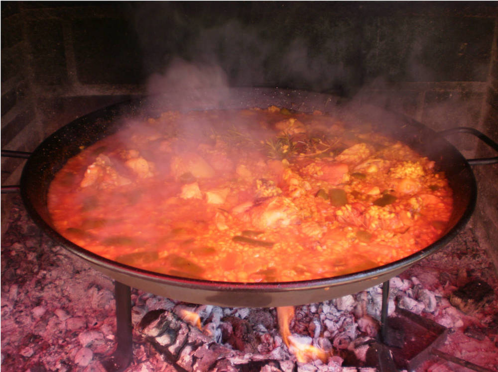 Paella valenciana is traditionally cooked outdoors, using orange firewood. (Photo by Rey de la Cruz)