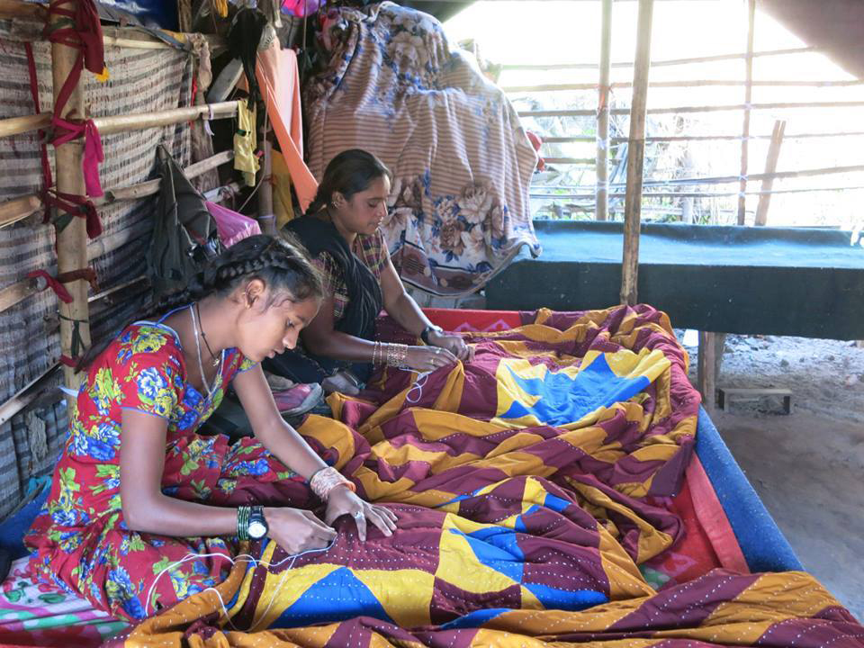 Mother and daughter finish up a quilt at their tent, in time for a shipment and which will fund the daughter's schooling. (Photo courtesy of Evelyn Domingo-Barker)