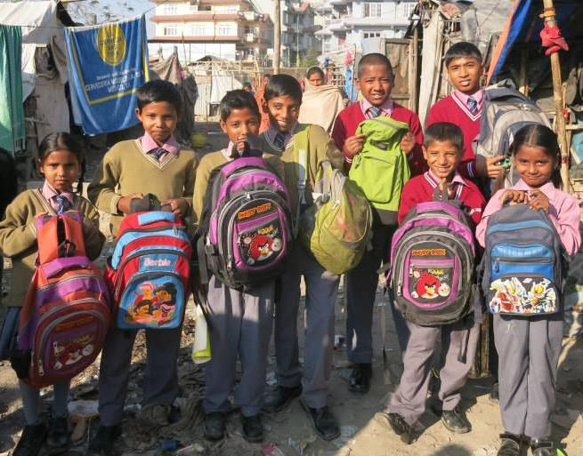 The camp children display their fresh backpacks, getting ready and looking forward to school. Other organizations also support the children by providing funds or organizing drives to collect donations of back-to-school supplies. (Photo courtesy of Evelyn Domingo-Barker)