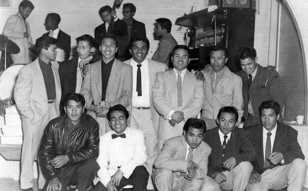 Bridge Generation young men posing at a wedding reception in Livingston in 1954.  Note the band members on break in the background, also BG contemporaries, who provided swing/jazz music for dancing. (Photo courtesy of Peter Jamero)