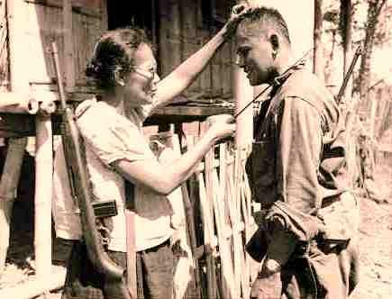 Nieves Fernandez, a school teacher-turned-Huk commander from Leyte, showing an American soldier how to kill Japanese soldiers with a bolo (Photo by Stanley Troutman courtesy of reddit.com)