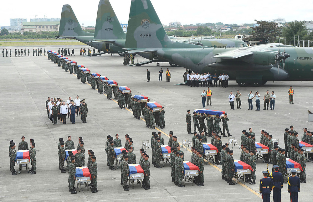 The Philippine National Police receive the remains of their fallen comrades at Villamor Air Base. Forty-four officers were killed in Mamasapano while in pursuit of two terrorists. (Source: AFP)