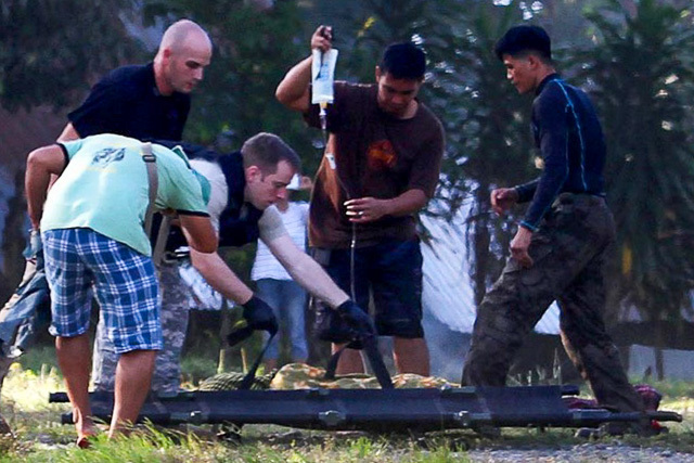 American military personnel assist Philippine soldiers load an injured police commando onto a waiting American helicopter at Mamasapano in Mindanao (Source: rappler.com/Photo by Mark Navales/AFP)